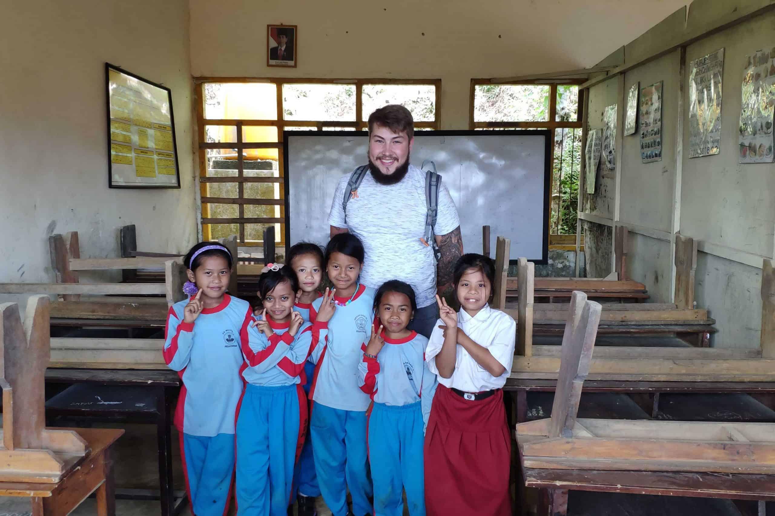 Die Schule haben wir 2019 im Rahmen des Projekteinsatzes gescoutet. (Daniel mit Schülerinnen. Bali 2019)